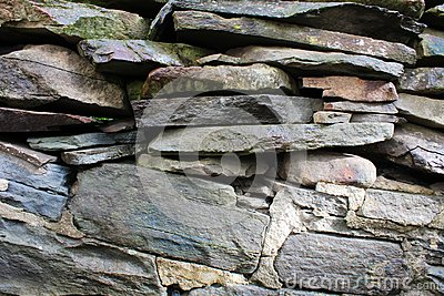 Stacked and mortared grey stone and flat rock wall