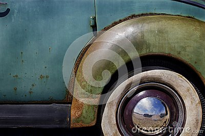 closeup of whitewall Tires, fender and hubcap on Old Vintage Car with peeling paint