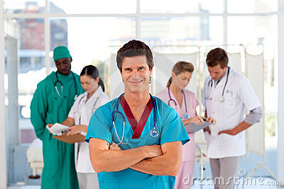 Smiling octor with his team in the background
