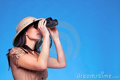 Woman in safari hat searching with binoculars