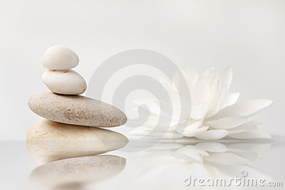 Stack of pebbles and white lily, reflection