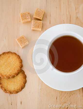 Cup of black tea, sugar and biscuits