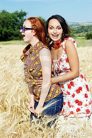 Two girls laughing in wheat field