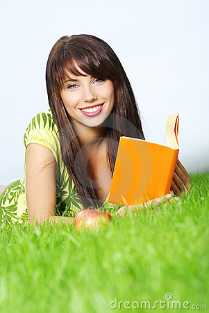 Woman lays on grass and reads book.