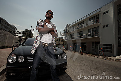 Stylish young male posing by a car