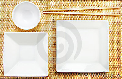White Plates and Chopsticks on a Bamboo Mat