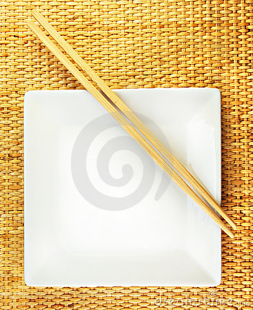 Square White Plate and Chopsticks on a Bamboo Mat