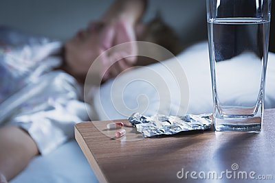 Sick woman takes capsule pill and drink water before sleeping