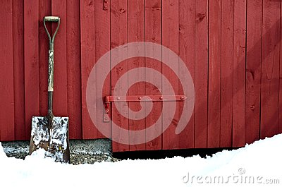 Old snow showel resting on red barn wall in snowy winter