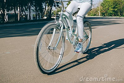 Girl in jeans rides a blue bike