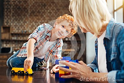 Beautiful blue eyed child looking at grandma while playing