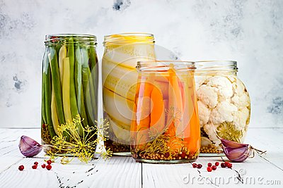 Marinated pickles variety preserving jars. Homemade green beans, squash, carrots, cauliflower pickles. Fermented food