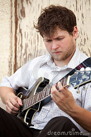 Young man playing guitar outdoors