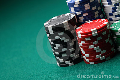 Stacks of poker chips on a green surface.