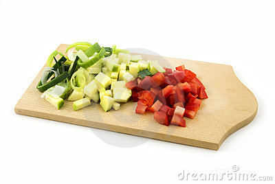 Wooden cutting board with various cut vegetables
