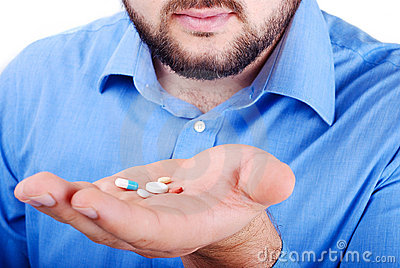 Mans palm with medicine pills on