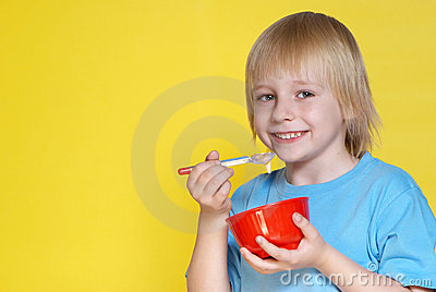 Nice boy with a bowl of corn-flakes