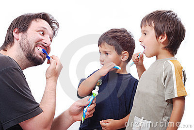 Young man teaching kids how to clean the teeth