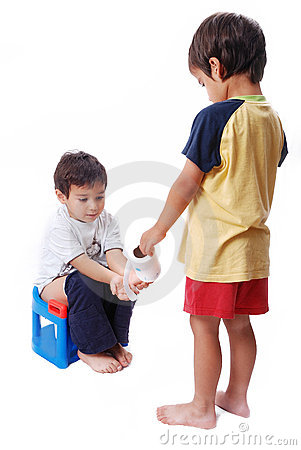 Kid is helping another one on toilet