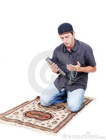 Muslim man is holding holly book Qoran and praying