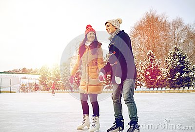 Happy couple ice skating on rink outdoors