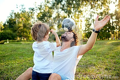 Father son playing with a ball on the grass in the park.