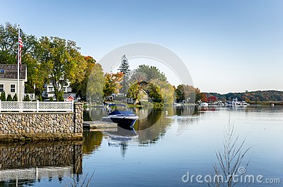 Waterside Houses and Boats Moored to Wooden Jetties under an Autumnal Clear Sky