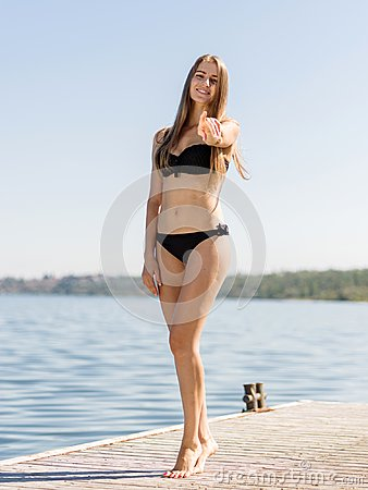Attractive sexy girl walking on pierce on a river background. Summer fashion concept.
