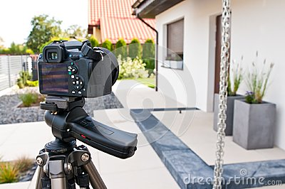 Shooting house exterior, photographer camera, tripod and ballhead