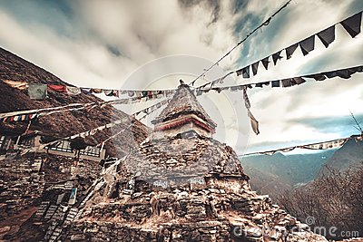 Prayer flags and buddhist stupa on trekking route