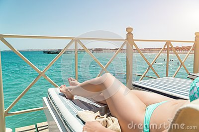 Women lower body lying with sunblock cream in shape for skin cancer sunburn care concept