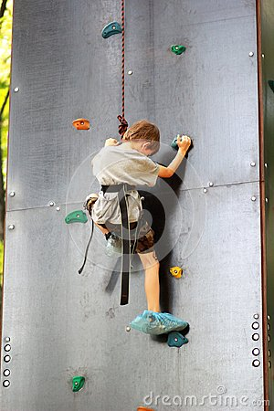 Five year old boy learning to climb the rock wall outside in the summer park.