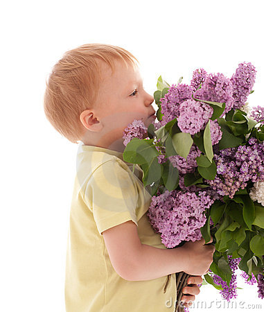 Portrait of boy smelling bouquet of lilac