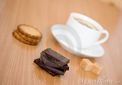 Cup of tea with lemon, biscuits and chocolate