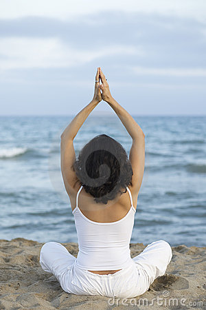 Woman making yoga exercise on the beach