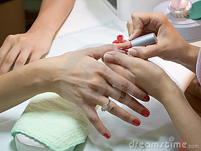 Manicurist putting red nail polish