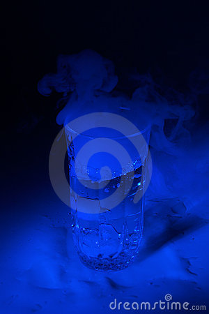 Blue lit water glass with dry ice