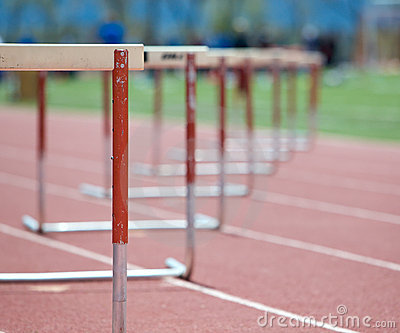 Hurdles lined up on a track, fading focus