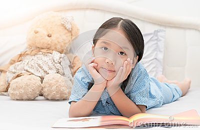 Cute little asian girl reading fairy tales book on bed