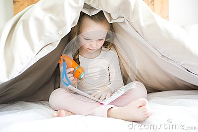 Little girl reading fairy tales book under the covers at the evening with lantern.