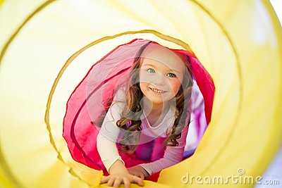 Happy child girl plays indoor in a tunnel