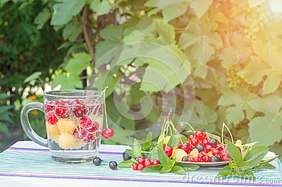 Berries cherries red and yellow in a glass with mineral water and on a plate.