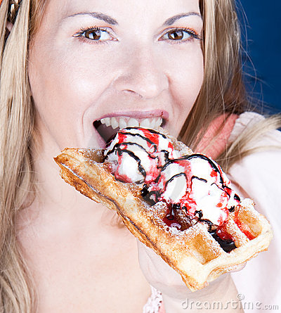 Beautiful woman  eating a  waffle with ice-cream