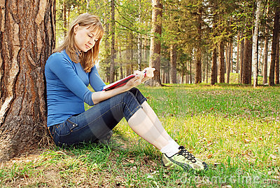 The young girl reads the book under a tree