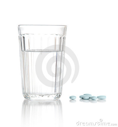 Glass with water and a heap of tablets, pills