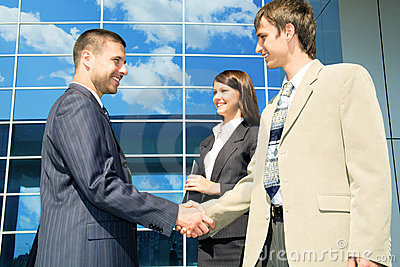 Handshaking in front of a modern building
