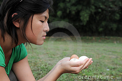Asian girl watches eggs
