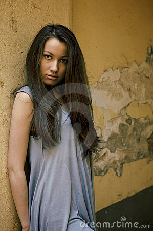 Young female model standing near the old wall