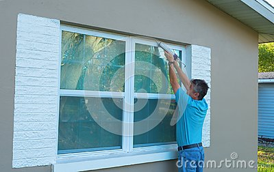 Homeowner caulking window weatherproofing home against rain and storms