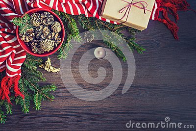 Top view of christmas decoration - red bowl full of fir-cones, gift box wrapped in kraft paper, golden angel, pine branches, candl